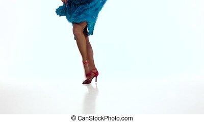 Legs of woman dancing elements of rumba in slow motion