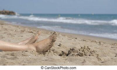 Legs of Woman Lying on Beach near the Sea. Woman lie on the...