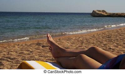 Legs of Woman Lying on Beach Sun Lounger near the Red Sea,...