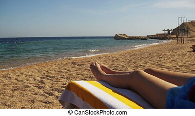 Legs of Woman Lying on Beach Sun Lounger near the Red Sea, Egypt