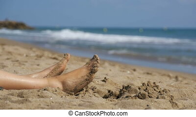 Legs of Woman Lying on the Beach near the Sea in Slow Motion...