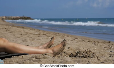 Legs of Woman Lying on the Beach near the Sea in Slow Motion