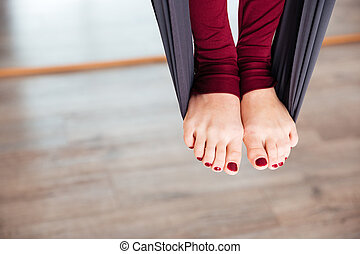 Legs of woman on hammock doing aerial yoga
