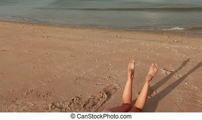 Leg's of woman relaxing on the beach