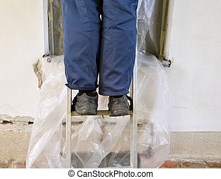 Legs of worker on the ladder.