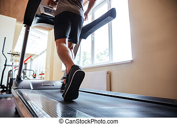 Legs of young man athlete running on treadmill in gym