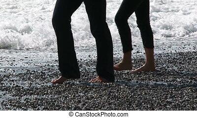 Two young men walking along the seashore.