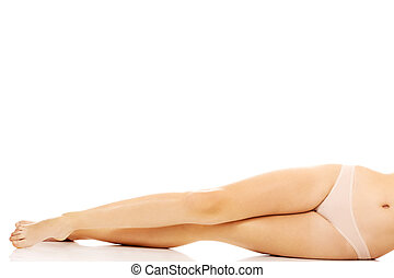 Legs of young woman lying on the floor