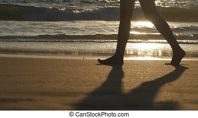 Legs of young woman stepping at sand. Close up of female feet walking on golden sand at the beach with ocean waves at background. Barefoot girl at the sea shore. Summer vacation holiday. Slow motion