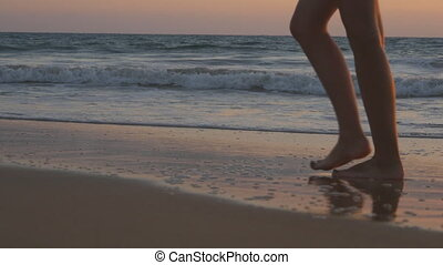 Legs of young woman traveler with backpack going along ocean beach during sunrise. Feet of female tourist walking barefoot on sea shore at sunset. Girl hiker stepping during travel or summer vacation