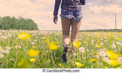 Legs of young woman walking through the meadow