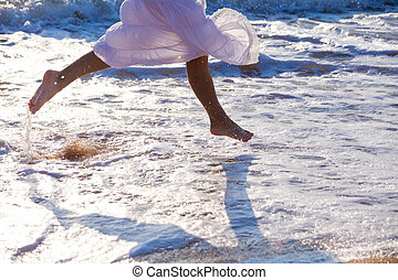 Legs of young woman who running on the surf