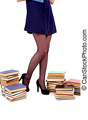 Legs of young woman with books isolated on white