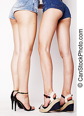 legs of young women, pair of butts in jeans shorts isolated...