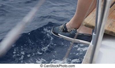 Legs on a yacht on background of waves.