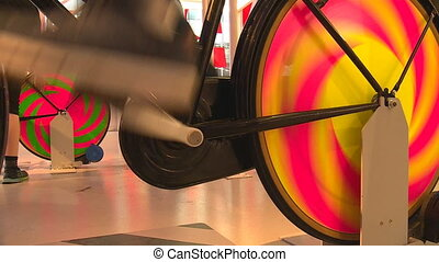Legs on colorful static pedal bicycle generating...