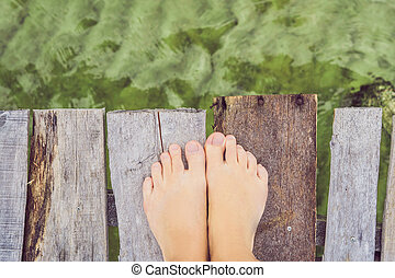 Legs on the old pier on the background of the sea