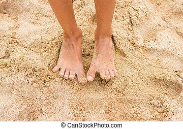 Legs slender seven-year girl standing barefoot on the sand