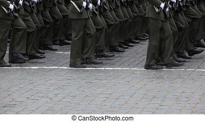 Legs soldiers march in rows on pavement at military parade...