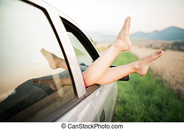 Legs sticking out of car window.