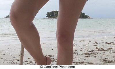 legs swinging on wooden swing on beach