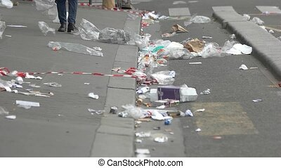 Legs walking on the street. Garbage on city road. Too much...