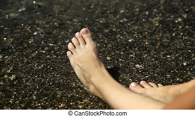 Legs washed by sea water. A lot of feet on the sandy beach....