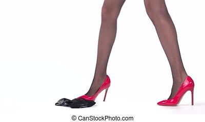 Legs wearing red heels. Woman putting on panties. Young sexy...
