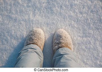 Legs, winter boots on snow