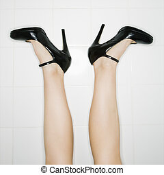 Caucasian female legs sticking up in air with high heels turned out.