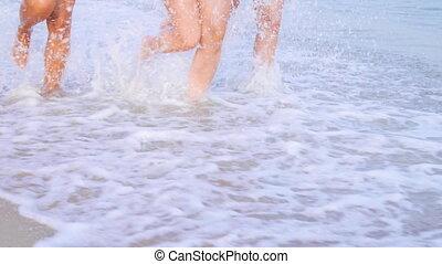 Legs womens tanned runing on sandy beach on sunset. Slim...