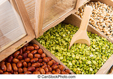 Legumes in shop shelf - Various dried legumes in wooden shop...