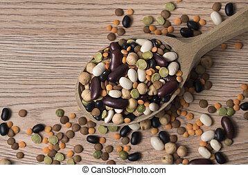 Legumes of various kinds in a wooden spoon on the table.