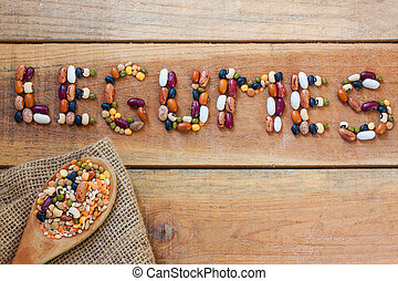 Legumes word with wood background