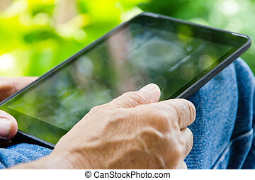 Senior man relaxing at home reading E-book on his tablet.