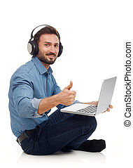 Leisure activity - Man with headphones and laptop looking at...