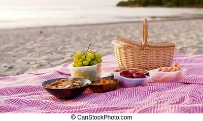 leisure and concept - food and picnic basket on blanket on beach