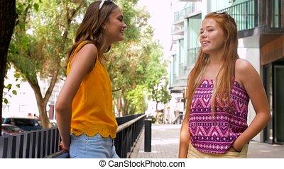teenage girls or friends talking in summer city - leisure...