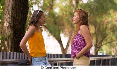 teenage girls or friends talking in summer park - leisure...