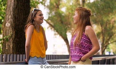 teenage girls or friends talking in summer park - leisure ...