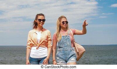 teenage girls or friends walking at seaside - leisure and...