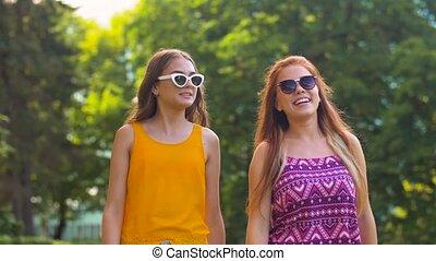 teenage girls or friends walking in summer park - leisure ...