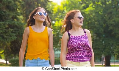 teenage girls or friends walking in summer park - leisure...
