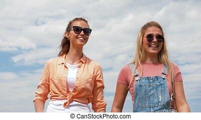 teenage girls or friends walking in summer - leisure and ...