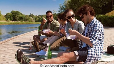 friends having picnic on lake pier - leisure and people ...