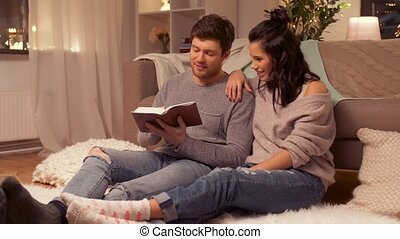 happy couple reading book at home - leisure and people...
