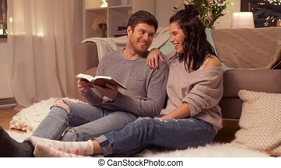 happy couple reading book at home