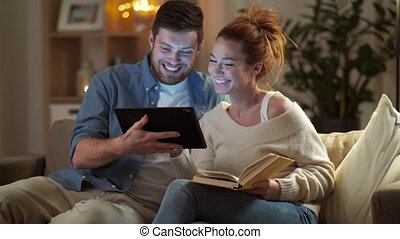 couple with tablet computer and book at home