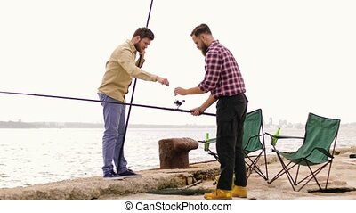 happy friends adjusting fishing rods on pier - leisure and...