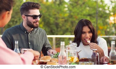 happy friends eating at rooftop party - leisure and people...